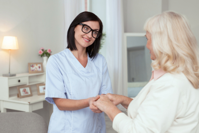 female caregiver wearing glasses while taking elder woman hands