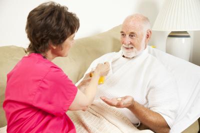 Home health nurse giving an elderly patient juice to make his medicine go down
